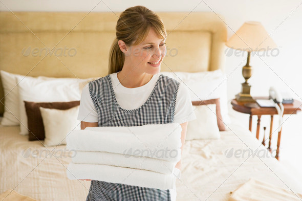 Maid holding towels in hotel room smiling - Stock Photo - Images