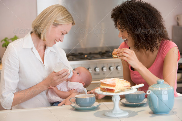 Mother and baby in kitchen with friend eating cake and smiling - Stock Photo - Images
