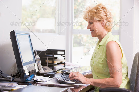 Woman in home office at computer smiling - Stock Photo - Images