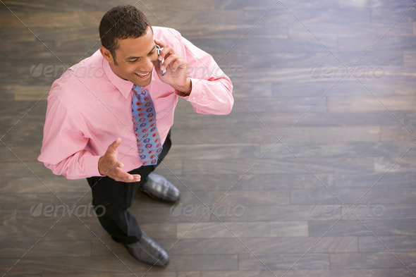 Businessman standing indoors using cellular phone smiling - Stock Photo - Images