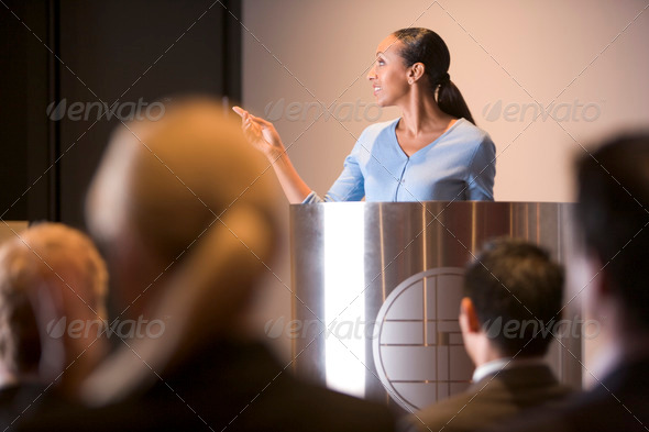 Businesswoman giving presentation at podium - Stock Photo - Images