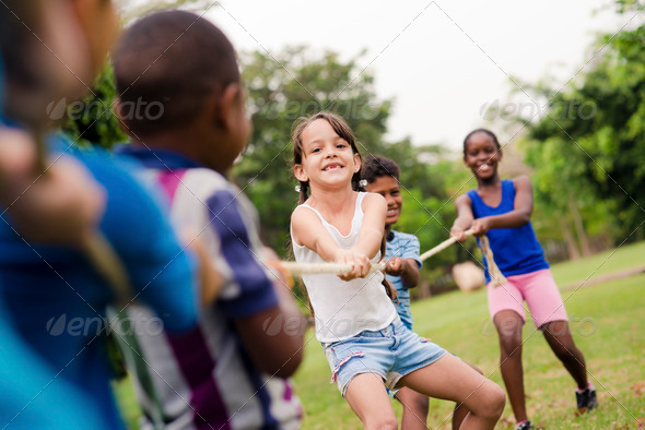 Happy school children playing tug of war with rope in park - Stock Photo - Images