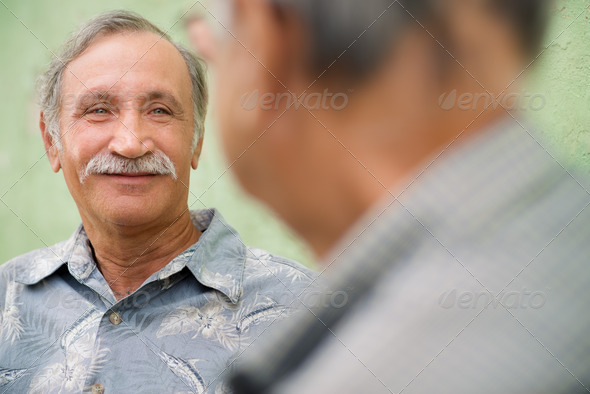 Two senior friends meeting and talking in park - Stock Photo - Images