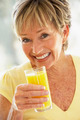 Woman Smiling At Camera Drinking Orange Juice - PhotoDune Item for Sale