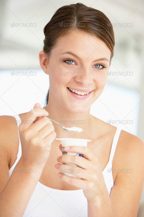 Young Woman Eating Yogurt - Stock Photo - Images