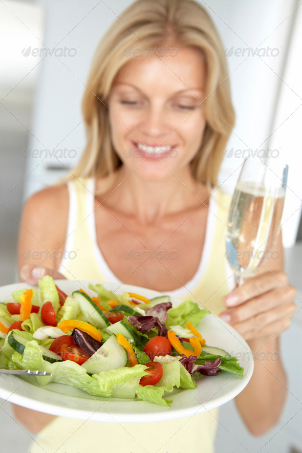 Mid Adult Woman Holding A Wine Glass And Fresh Salad - Stock Photo - Images