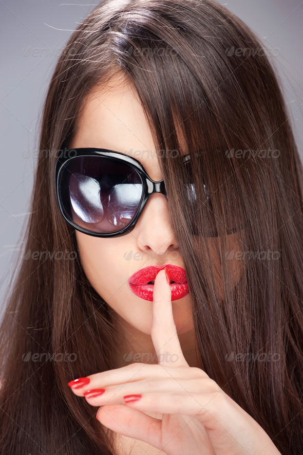 woman showing the sign for silence with her index finger - Stock Photo - Images