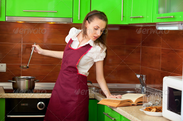 Housewife is preparing soup with book - Stock Photo - Images
