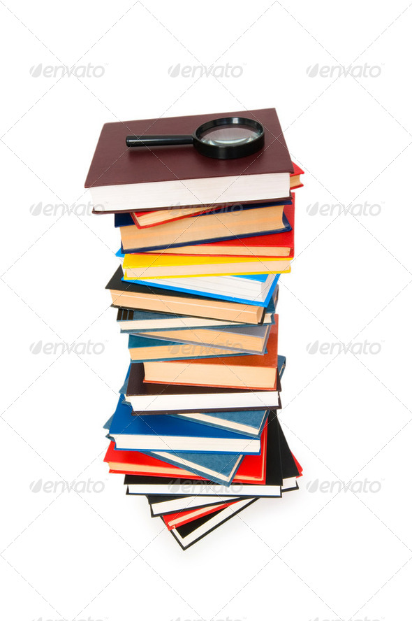 Magnifying glass over the stack of books - Stock Photo - Images