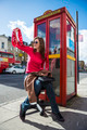 Young woman waving with london red phone booth at back - PhotoDune Item for Sale