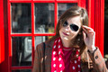 Fashionable young woman leaning on red phone booth - PhotoDune Item for Sale
