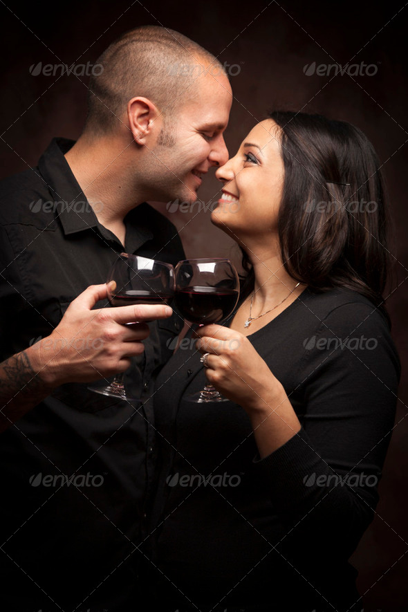 Happy Mixed Race Couple Flirting and Holding Wine Glasses on a Dark Background. - Stock Photo - Images