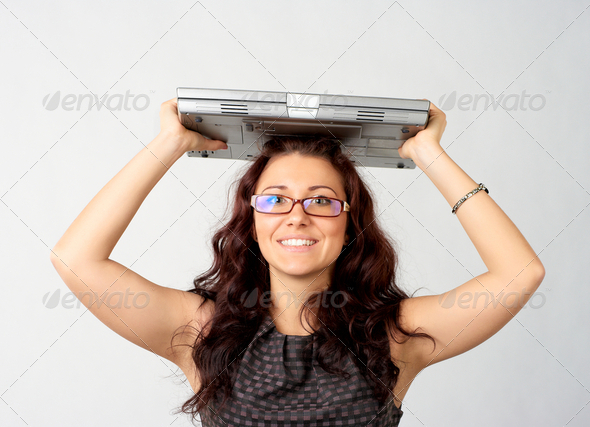 Portrait of young woman holding a laptop above her head - Stock Photo - Images