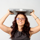 Portrait of young woman holding a laptop above her head - PhotoDune Item for Sale