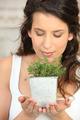 Woman smelling a herb pot
