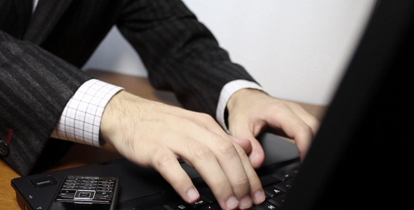 Businessman Typing On Laptop Keyboard
