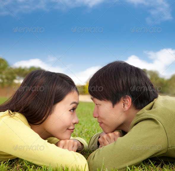 Happy asian couple lying on the grass with cloud background - Stock Photo - Images