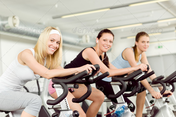 Fitness young woman on gym bike spinning - Stock Photo - Images