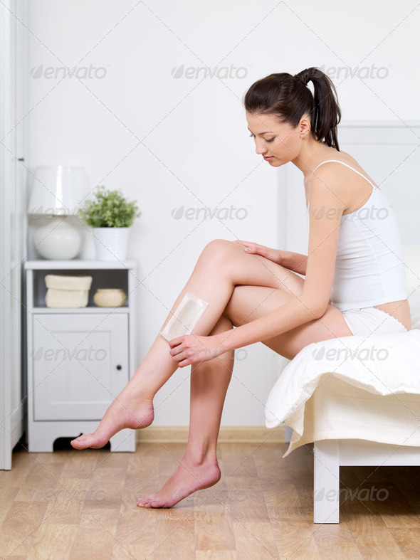 Woman depilating her attractive legs by waxing - Stock Photo - Images