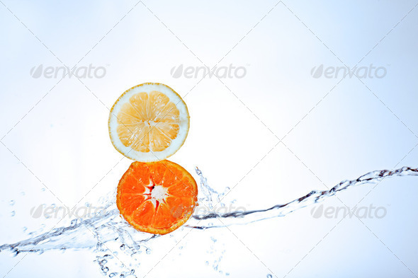 Fresh tangerine and lemon splashing underwater - Stock Photo - Images