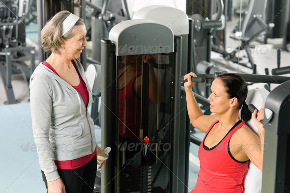 Personal trainer at fitness center showing exercise - Stock Photo - Images