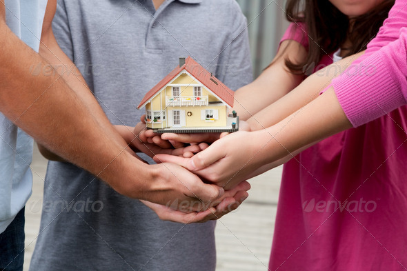 Human hands holding a model of house - Stock Photo - Images