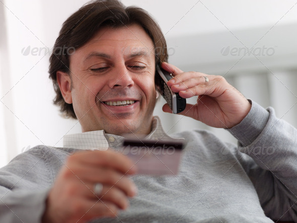 adult man shopping from home with telephone and credit card - Stock Photo - Images