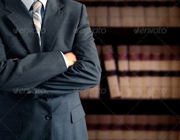 Businessman in front of bookcase - Stock Photo - Images