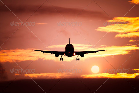 plane in the sunset sky - Stock Photo - Images