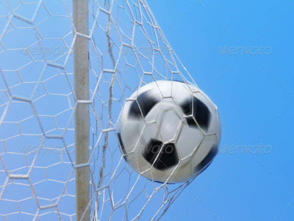 Football spinning in goal against blue sky - Stock Photo - Images
