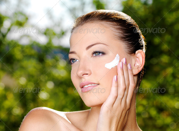Beautiful woman applying cream on cheek - Stock Photo - Images