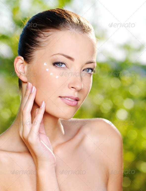 Beautiful woman applying cream near eyes - Stock Photo - Images