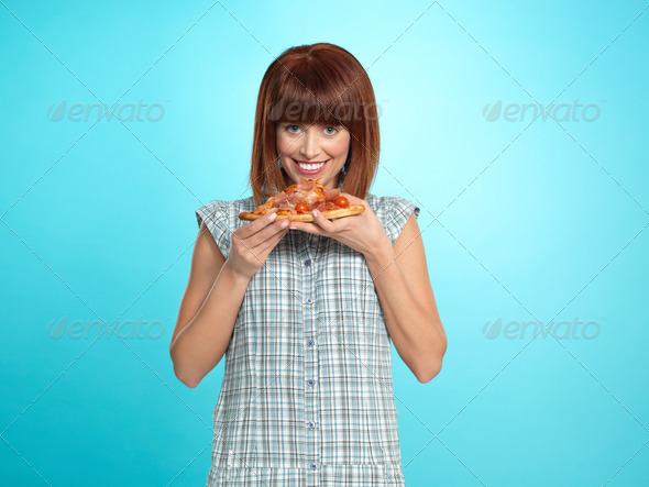 beautiful young woman eating a pizza pie - Stock Photo - Images