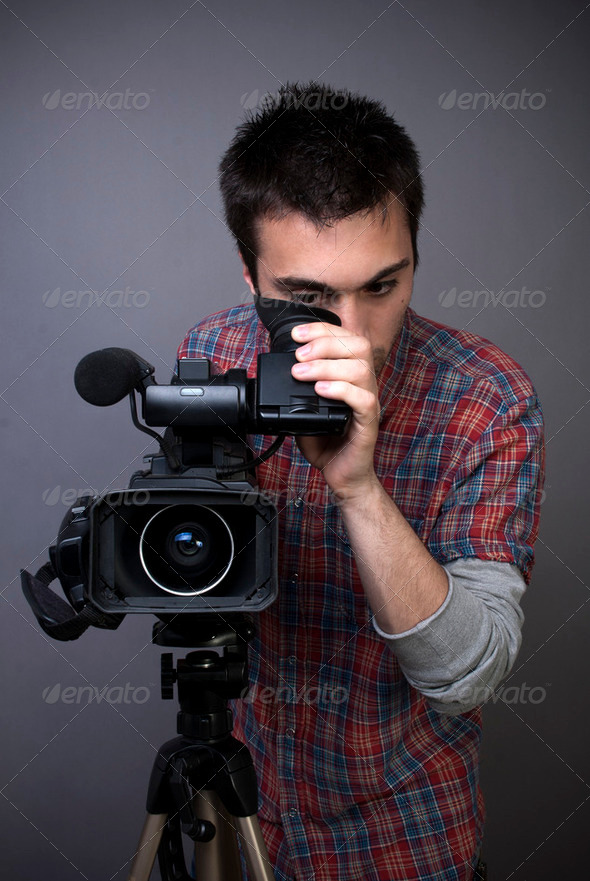 Young man with professional video camcorder - Stock Photo - Images