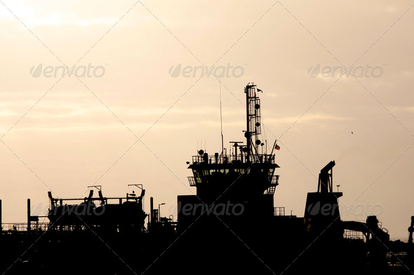 Silhouette of a ship against a sunset sky - Stock Photo - Images