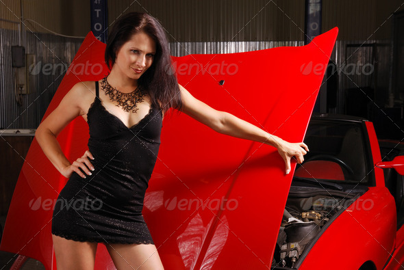 Pretty woman against the lifted hood of a sport car. - Stock Photo - Images