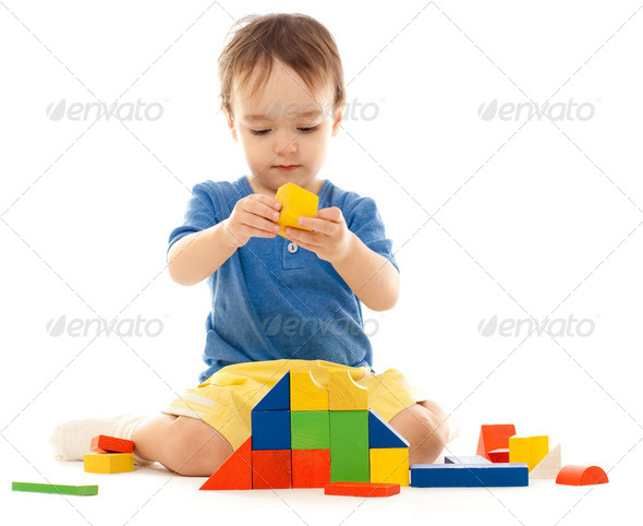 Cute little boy is playing with colorful building wooden blocks - Stock Photo - Images