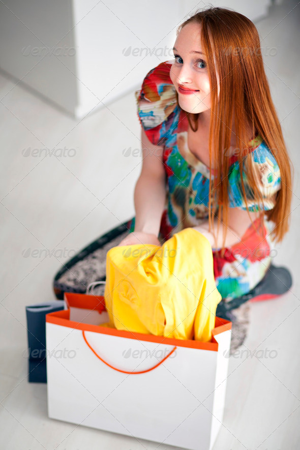 Young beautiful female holding and looking dresses - Stock Photo - Images