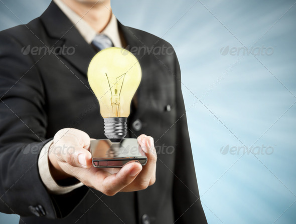 Businessman holding mobile phone light bulb coming out  technolo - Stock Photo - Images