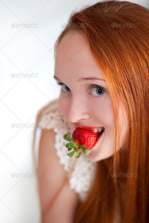 Young beautiful long haired woman eating ripe strawberry - Stock Photo - Images