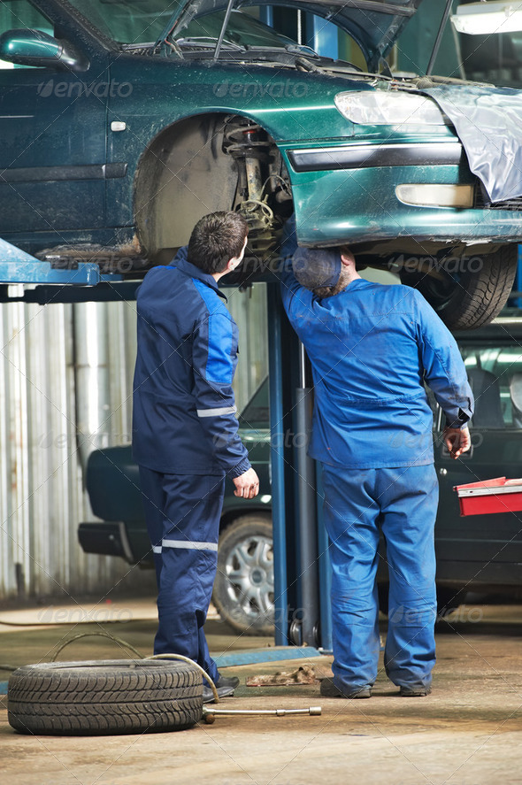 two car mechanic diagnosing auto suspension - Stock Photo - Images