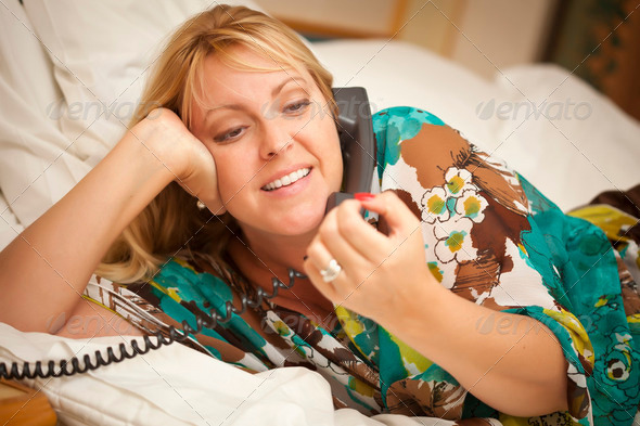 Beautiful Blonde Woman Laying on Her Bed Using the Telephone. - Stock Photo - Images