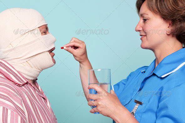 Nurse giving a patient some medicine - Stock Photo - Images