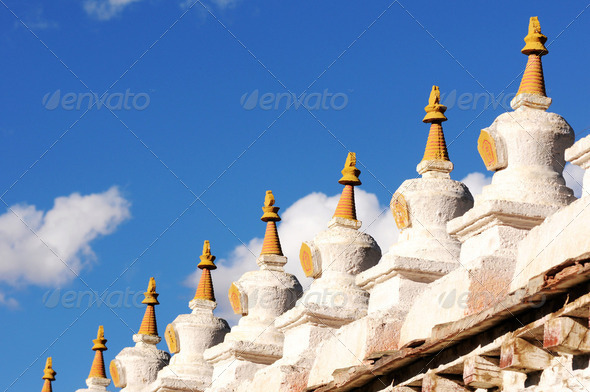 Landmark of historic white stupa in a Tibetan lamasery against blue sky - Stock Photo - Images