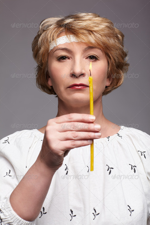 senior woman with candle - Stock Photo - Images