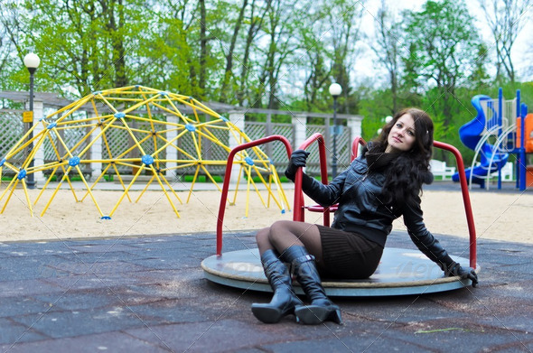 Attractive girl girl in a jacket on the playground - Stock Photo - Images