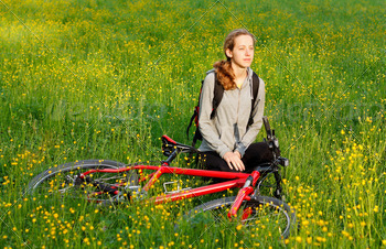 Woman cyclist with bike and backpack among the blooming meadow