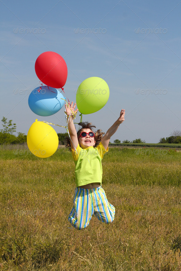 Happy little girl jumping with balloons on meadow - Stock Photo - Images