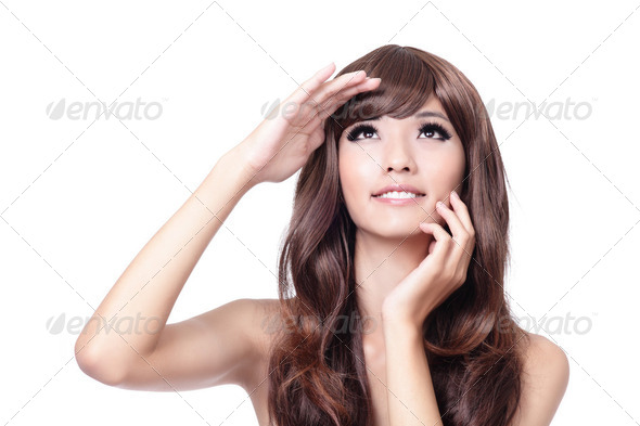 young woman touching her face and looking up - Stock Photo - Images