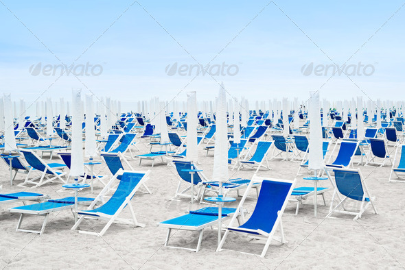 Beach umbrellas and blue deckchairs - Stock Photo - Images